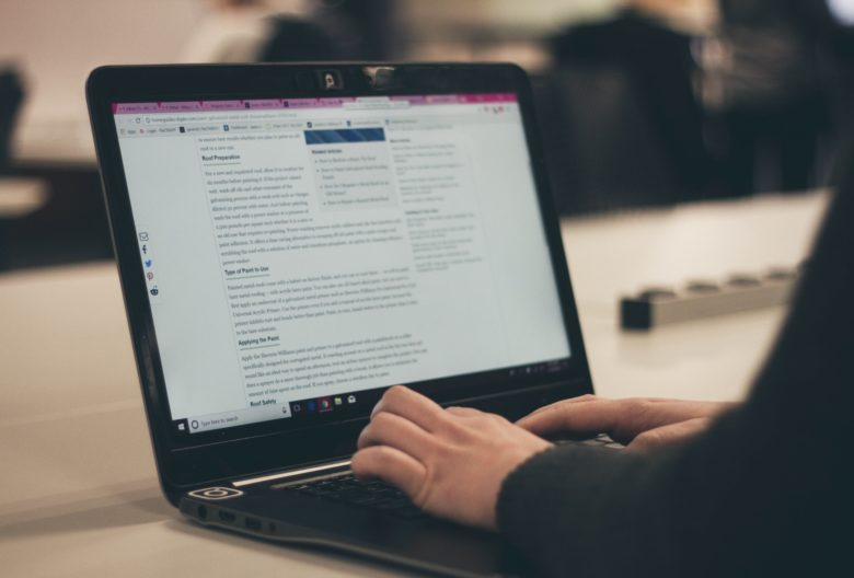 Woman writing a guest blog on a website on a laptop to help with SEO